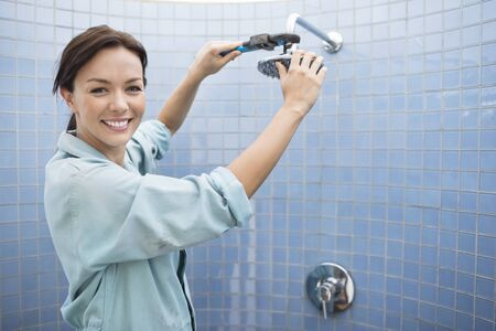 handywoman: Female plumber working on shower head in bathroom