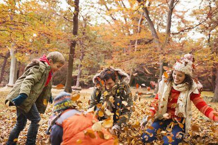 arrodillarse: Familia jugando en las hojas de otoño en el parque LANG_EVOIMAGES