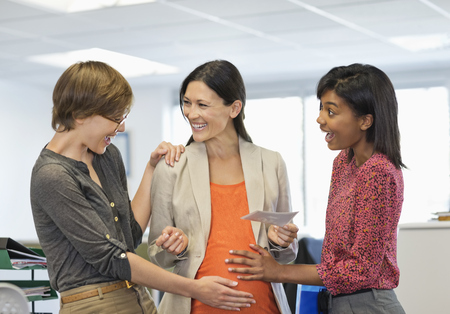 admiring: Colleagues admiring pregnant businesswoman's belly LANG_EVOIMAGES