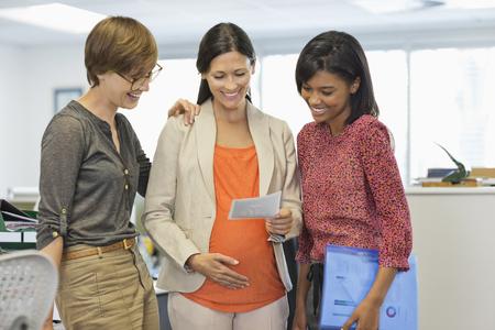 sonograma: Pregnant businesswoman showing colleagues sonogram LANG_EVOIMAGES