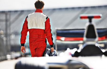 racetrack: Racer carrying helmet on track