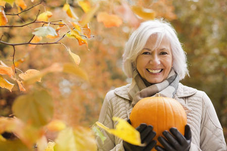 smile close up: Older woman holding pumpkin in park