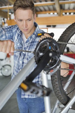 domestic garage: Man working on bicycle in shop