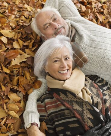 looking away from camera: Older couple laying in autumn leaves LANG_EVOIMAGES