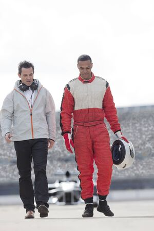 formula one: Racer and manager walking on track
