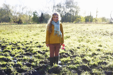 looking away from camera: Smiling girl standing in muddy field LANG_EVOIMAGES