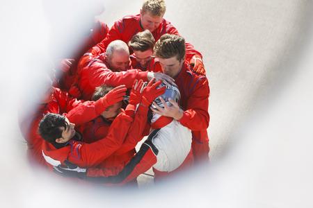 Racing team hugging racer at pit stop