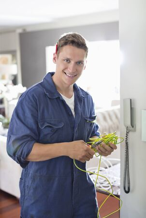 cable tangle: Electrician working on telephone in home