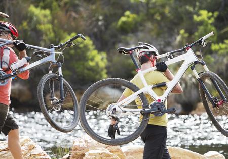 riverbank: Men carrying mountain bikes in river