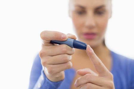 Woman taking her own blood sugar LANG_EVOIMAGES