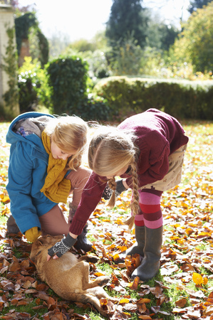 Girls petting dog in autumn leaves LANG_EVOIMAGES