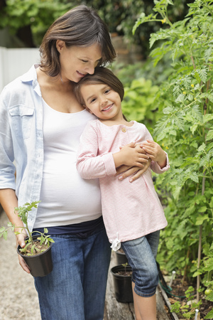 smile close up: Pregnant mother and daughter gardening together
