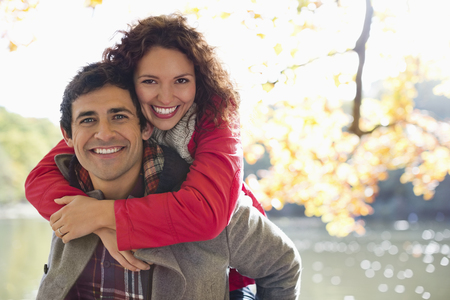 looking away from camera: Man carrying girlfriend piggyback in park