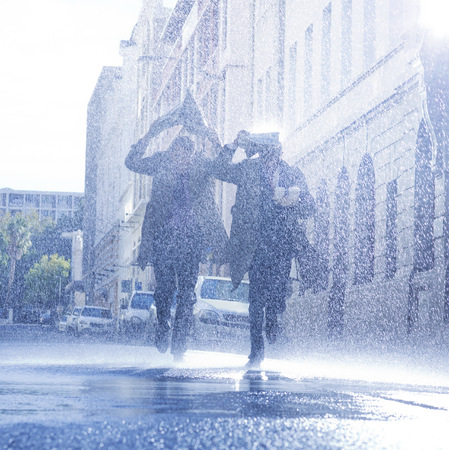 jamaican man: Businessmen covering heads with newspaper in rain LANG_EVOIMAGES
