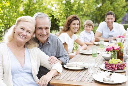 family: Family smiling at table outdoors