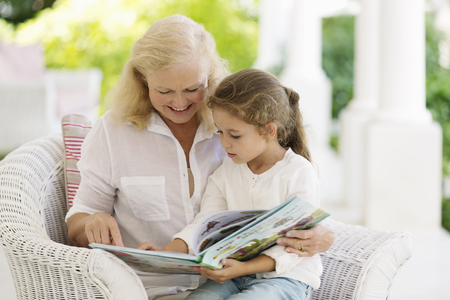 storybook: Older woman reading to granddaughter on porch