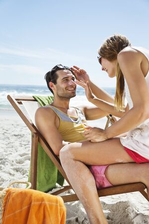 Woman applying sunscreen to mans nose at beach LANG_EVOIMAGES