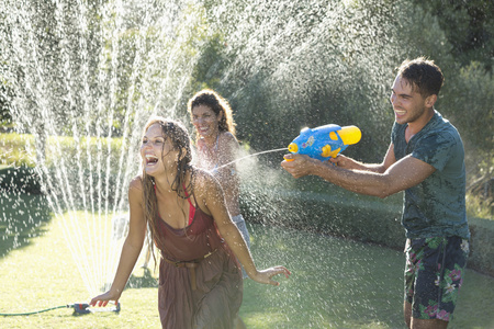 wetting: Friends playing with water guns in sprinkler in backyard