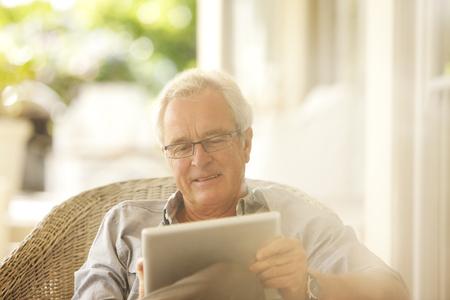 silver surfer: Senior man using digital tablet on patio LANG_EVOIMAGES