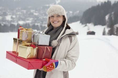 Portrait of smiling woman carrying Christmas gifts in snowy field