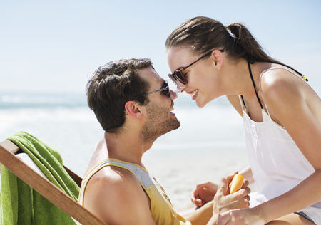 Happy couple rubbing sunscreen-covered noses on beach