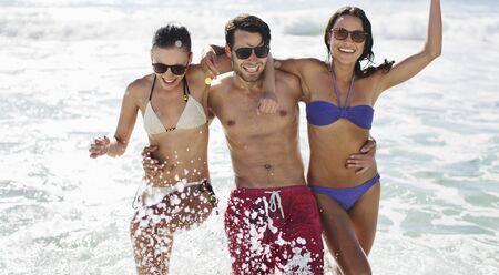 kick around: Portrait of enthusiastic friends splashing in ocean