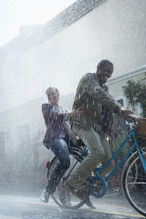 jamaican adult: Happy couple riding bicycle in rainy street