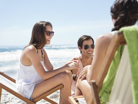 Friends hanging out at beach LANG_EVOIMAGES
