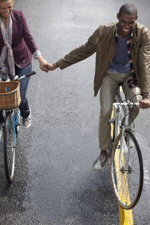 jamaican adult: Happy couple holding hands and riding bicycles LANG_EVOIMAGES