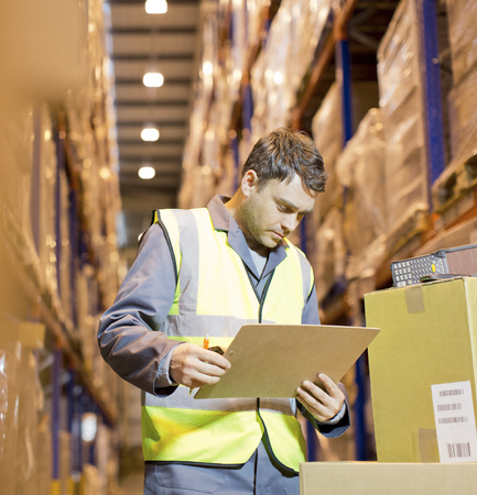 Worker reading clipboard in warehouse LANG_EVOIMAGES