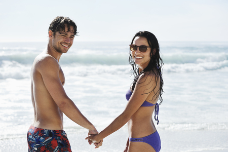 turn away: Portrait of happy couple holding hands on beach