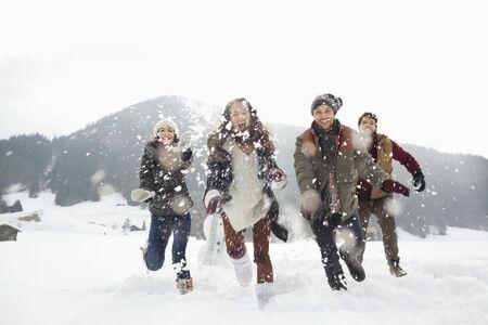 Joyeux amis jouant dans un champ enneigé