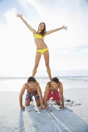 looking away from camera: Portrait of woman standing on mens back on beach LANG_EVOIMAGES