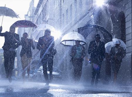 jamaican man: Business people with umbrellas running in rain