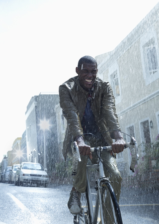 jamaican man: Happy businessman riding bicycle in rain