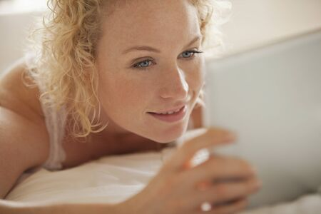 electronic book: Close up of woman using digital tablet in bed