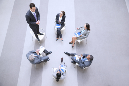 round chairs: High angle view of businessman standing on chair in circle with co-workers LANG_EVOIMAGES