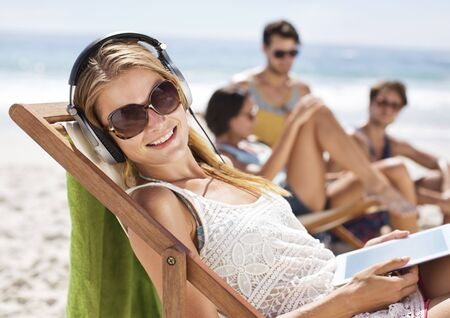 electronic book: Portrait of happy woman listening to headphones at beach