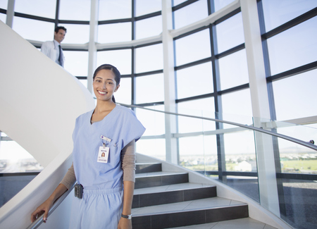 Portrait of smiling nurse on stairs