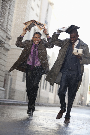 jamaican man: Businessmen with coffee covering heads with newspaper in rainy street