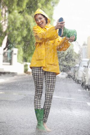 Portrait of enthusiastic woman emptying boot in rain LANG_EVOIMAGES