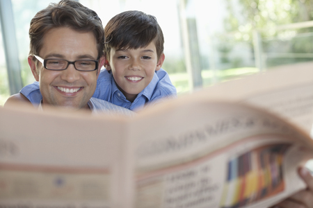 smile close up: Father and son reading newspaper together