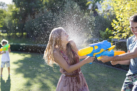 Couple playing with water guns in backyard