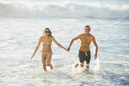 looking away from camera: Portrait of happy couple holding hands and running in ocean