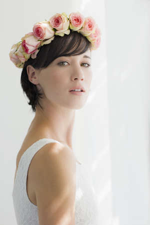 Portrait of serious bride wearing rose wreath on head LANG_EVOIMAGES