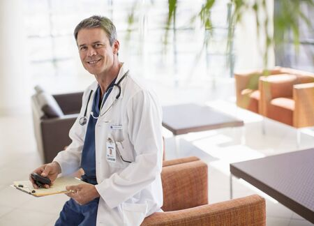 pager: Portrait of smiling doctor in hospital lobby