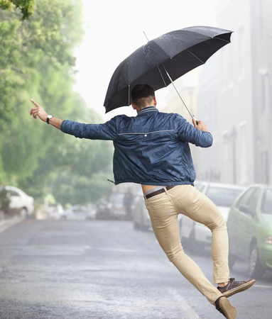 Man dancing with umbrella in rainy street