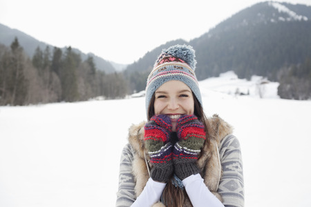 looking away from camera: Portrait of enthusiastic woman wearing knit hat and gloves in snowy field