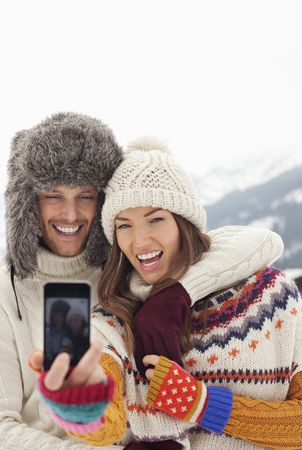 looking away from camera: Enthusiastic couple taking self-portrait with camera phone