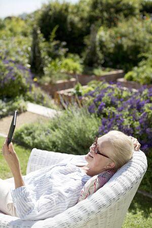 silver surfer: Senior woman using digital tablet in garden